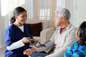 caregiver monitoring his patients blood pressure